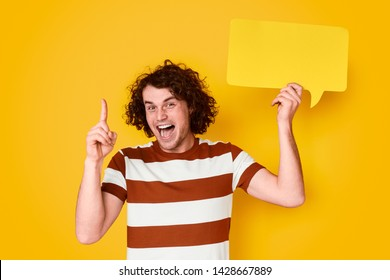 Cheerful young male with curly ginger hair pointing up and holding empty speech bubble with blank space for quote against vivid yellow background