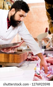 Cheerful young male seller cutting meat to sell in butcher's shop