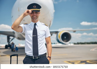 Cheerful young man airline worker touching captain hat and smiling while standing in airfield with airplane on background