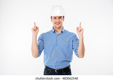 Cheerful young man architect in hard hat pointing up with both hands