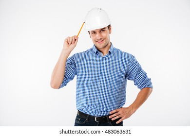 Cheerful young man architect in hard hat standing and holding pencil