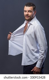 Cheerful young man with beard is standing and posing. He is flirting and touching his white shirt playfully. The man is looking forward with desire and smiling. Isolated on grey background