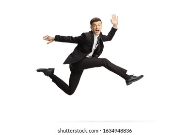 Cheerful young man in a black suit jumping and looking at camera isolated on white background
