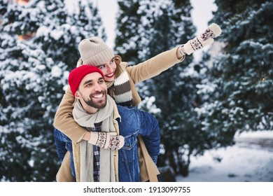 Cheerful young man is carrying beloved woman while they are having fun in nature in winter