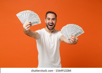 Cheerful young man in casual white t-shirt posing isolated on bright orange wall background studio portrait. People lifestyle concept. Mock up copy space. Hold fan of cash money in dollar banknotes