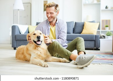 Cheerful young man in casualwear relaxing at home and playing with friendly purebred golden labrador