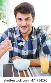 Cheerful young man in checkered shirt eating cereals with milk for breakfast on the kitchen