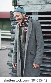 Cheerful young man in a coat and hat in an urban environment in the outdoor. Cheerful male hipster laughing.Lifestyle