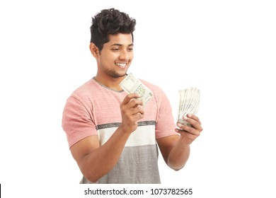 Cheerful young man counting Indian rupees on white.