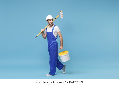 Cheerful young man in coveralls protective helmet hardhat hold paint roller, bucket isolated on pastel blue wall background. Instruments accessories for renovation apartment room. Repair home concept