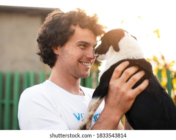 Cheerful young man with curly hair smiling while stray puppy licking nose on sunny day in dog shelter yard
