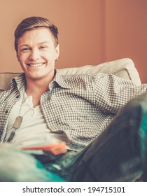 Cheerful young man with dog  tag in home interior