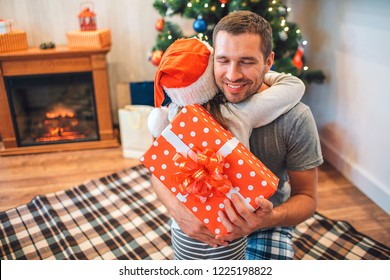 Cheerful young man embrcing his child and and smiling. He holds pesent that got from daughter. She wears red hat. They are in decorated room woth fireplace and Christmas tree.