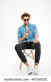 Cheerful young man in hat and sunglasses sitting and using smartphone over white background
