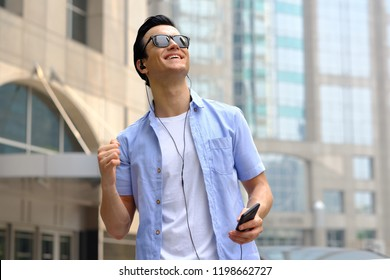 cheerful young man listening to music with headphones. Happy smiling young man listening to music from mobile phone in city background. Handsome caucasian man on summer holiday vacation travel concept