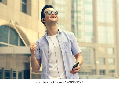 cheerful young man listening to music with headphones. Happy smiling young man listening to music from mobile phone in city background. Handsome caucasian man with cellphone, tourist on street.