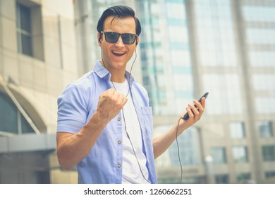 cheerful young man listening to music with headphones.Happy smiling young man listening to music from mobile phone in city background.tourist on street, tourism,summer holiday vacation travel concept.