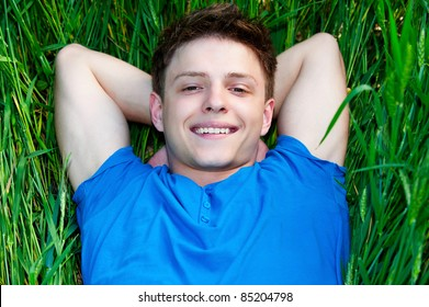 cheerful young man lying on green field