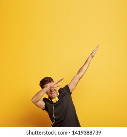 Cheerful young man makes dab dance gesture, shows dabbing movement, has fun in club, uses modern headphones for listening music, isolated over yellow background with free space above. Dance pose
