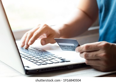 Cheerful young man paying bills online with credit card and laptop.