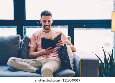 Cheerful young man reading interesting bestseller sitting on couch in comfortable apartment enjoying leisure time on weekend.Positive hipster guy with literature book in hands sitting on sofa