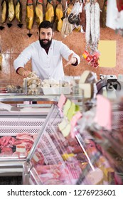 Cheerful young man seller in butcher's shop