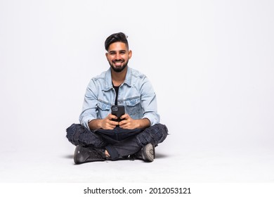 Cheerful young man sitting with legs crossed isolated over white background, using mobile phone