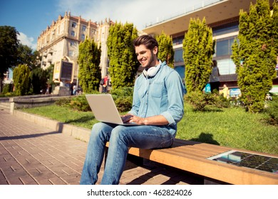 cheerful young man  sitting on bench with laptop and solar cell