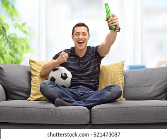 Cheerful young man sitting on a sofa watching football and having a beer