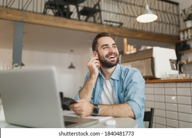 Cheerful young man sitting at table in coffee shop cafe restaurant indoors working studying on laptop pc computer listening music with air pods cell phone. Freelance mobile office business concept