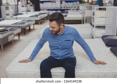Cheerful young man smiling, sitting on a new bed at furniture store. Attractive male customer buying orthopedic mattress at furnishings shop. Relaxation, home, living concept
