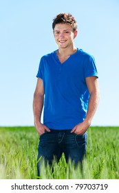 cheerful young man standing in green field