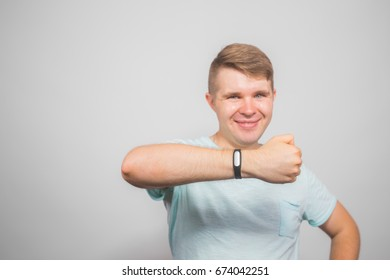 Cheerful young man standing and pointing on fitness tracker over grey background