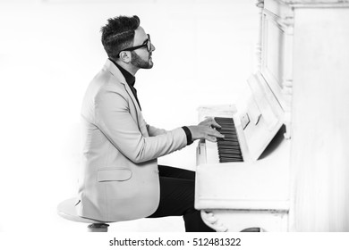 Cheerful young man in stylish suit is playing piano