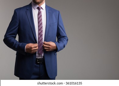 Cheerful young man in suit is preparing for an appointment. He is standing and touching his jacket. Isolated and copy space in right side