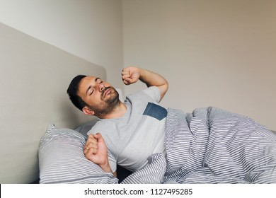 Cheerful young man is waking up after sleeping in the morning