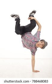 Cheerful young man wearing casual shirt dancing sitting on one hand, performing breakdance moves on wood floor upside down, with legs up. Vertical image in studio on white background.