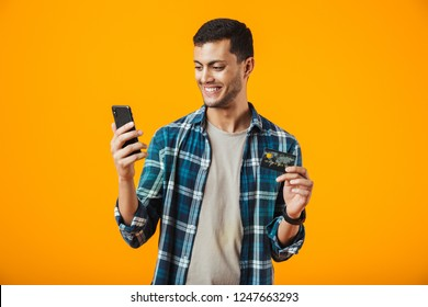 Cheerful young man wearing plaid shirt standing isolated over orange background, holding mobile phone, showing plastic credit card