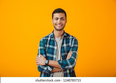 Cheerful young man wearing plaid shirt standing isolated over orange background, arms folded