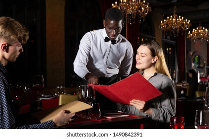 Cheerful young man and woman with menu ordering food in luxury restaurant