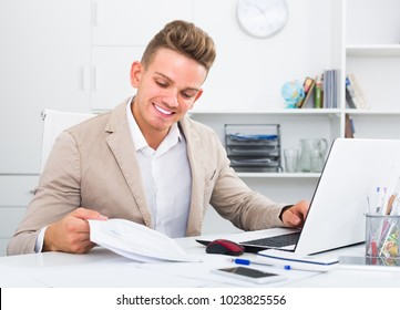 cheerful young manager working efficiently at office desk with laptop