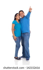 cheerful young married indian couple pointing on white background