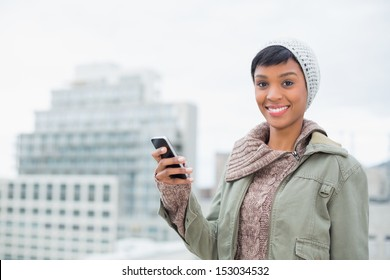 Cheerful young model in winter clothes holding her mobile phone outside on a cloudy day