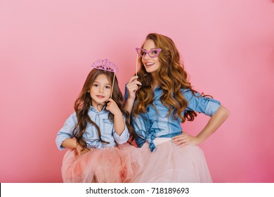 Cheerful young mother and daughter fooling around wearing crown and carnival mask at family party. Two charming sisters in same vintage outfit playing together and smiling on pink background