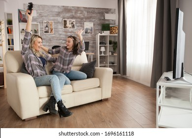 Cheerful young mother and her daughter about video games. Wireless controller.
