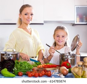 Cheerful young mother and little daughter preparing vegetables in slow-cooker