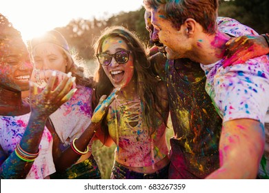 cheerful young multiethnic friends with colorful paint on clothes and bodies having fun together at holi festival