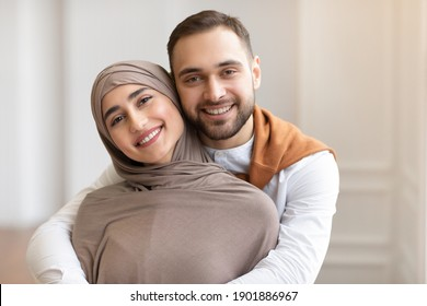Cheerful Young Muslim Couple Hugging Posing Smiling To Camera Standing Indoors At Home. Arab Spouses In Love. Happy Arabic Family Portrait. Happiness In Marriage And Romantic Relationship Concept