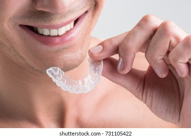 Cheerful young nude guy is holding plastic transparent brace