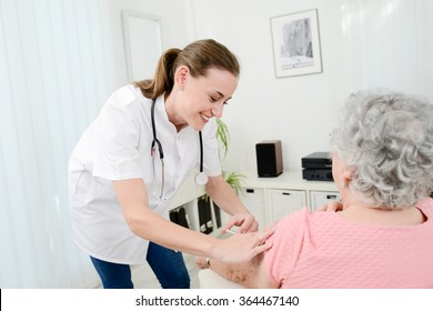 cheerful young nurse giving a vaccine injection to elderly woman at home
